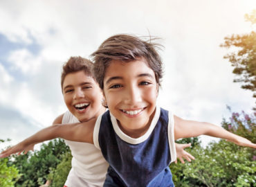 Happy brothers having fun outdoors, playing as if flying, two active boys spending summer holidays with pleasure in a countryside